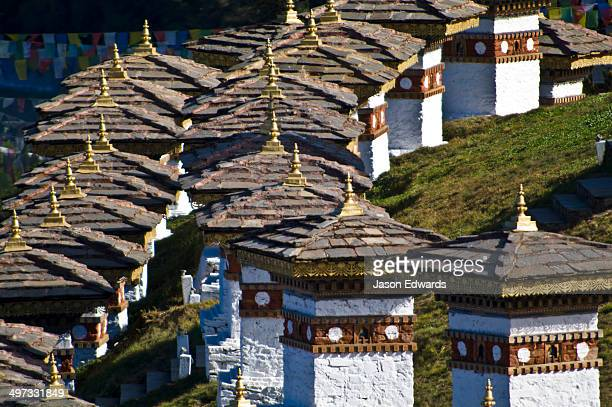 The tiled roofs and golden spires of chortens catch the afternoon sun.