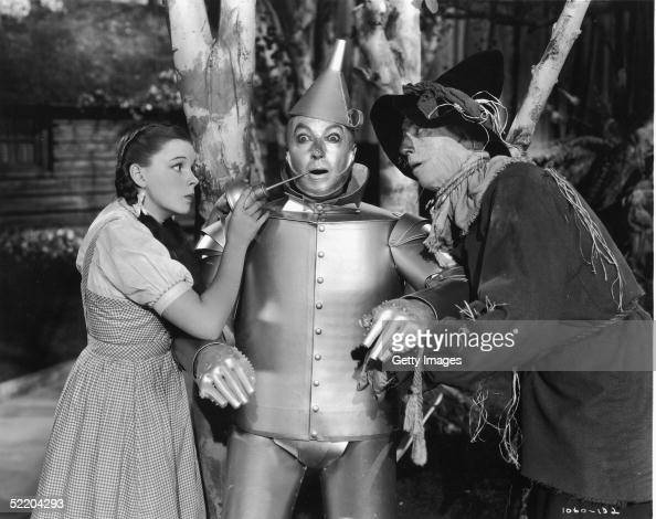 The Tin Man recieving some essential maintenence from his friends Dorothy and The Scarecrow in a scene from Victor Fleming's 1939 film 'The Wizard of...