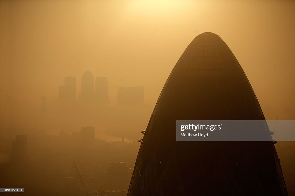 The tip of the Gherkin is silhouetted at sunrise in front of the Canary Wharf skyline at sunrise on March 5, 2013 in London, England. The recent construction of numerous tall buildings on the London skyline has been controversial due to concerns that views of historic landmark buildings, such as St Paul's cathedral, are being obscured.