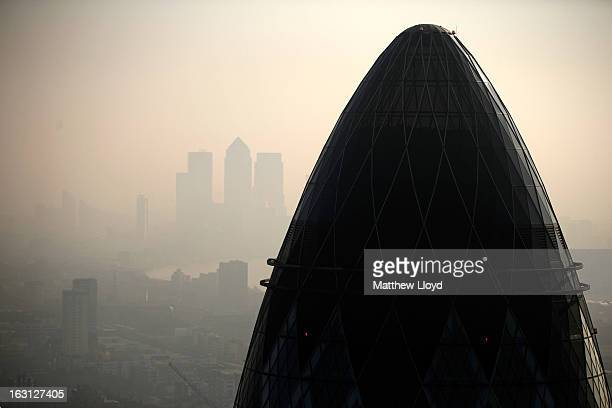 The tip of the Gherkin is silhouetted at sunrise in front of the Canary Wharf skyline at sunrise on March 5 2013 in London England The recent...