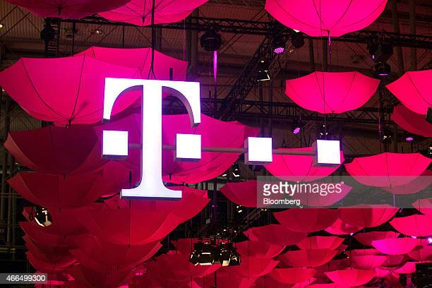 The TMobile logo for Deutsche Telekom AG's TSystems unit is seen suspended from the ceiling along with a collection of coloured umbrellas during the...