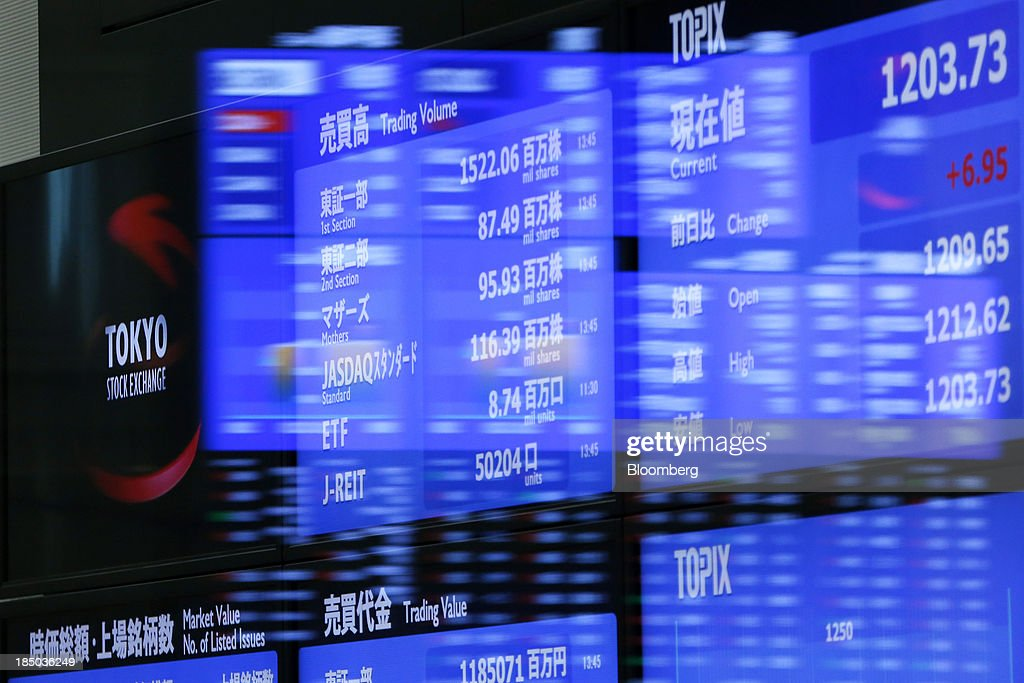 The Tokyo Stock Exchange (TSE) logo, left, is displayed alongside stock figures on an electronic stock board at the bourse in Tokyo, Japan, on Thursday, Oct. 17, 2013. Japanese shares rose, with the Topix index climbing to a three-week high, after the U.S. Congress voted to end the government shutdown and raise the debt ceiling, ending the nation's fiscal impasse. Photographer: Kiyoshi Ota/Bloomberg via Getty Images