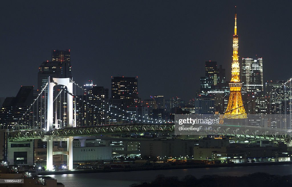 The Tokyo Tower, right, stands illuminated at night in Tokyo, Japan, on Wednesday, Jan. 23, 2013. Japan's exports fell more than analysts forecast and the annual trade deficit swelled to a record, bolstering the case for Prime Minister Shinzo Abe to weaken the yen even as trade tensions mount. Photographer: Tomohiro Ohsumi/Bloomberg via Getty Images