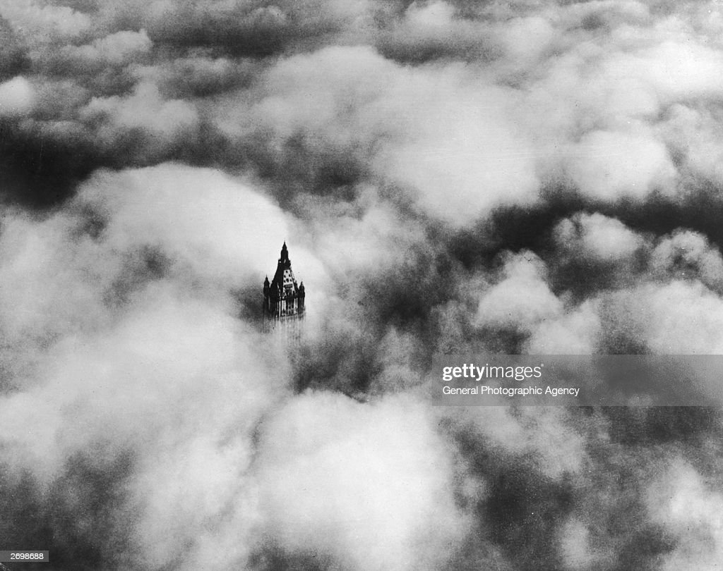 The top of the Woolworth Building in New York above the clouds. It was designed by Cass Gilbert and was the second tallest building in the world at the time of its completion.