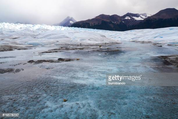 The top surface of Perito Moreno Glacier showing a river running through the ice, erosion, crevasses and turquoise hues.