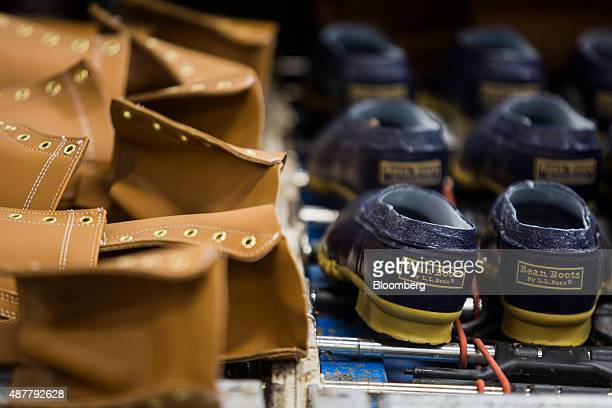 The tops and bottoms of boots move along a conveyor belt to a dryer which cures the glue during production at the LL Bean Inc manufacturing facility...