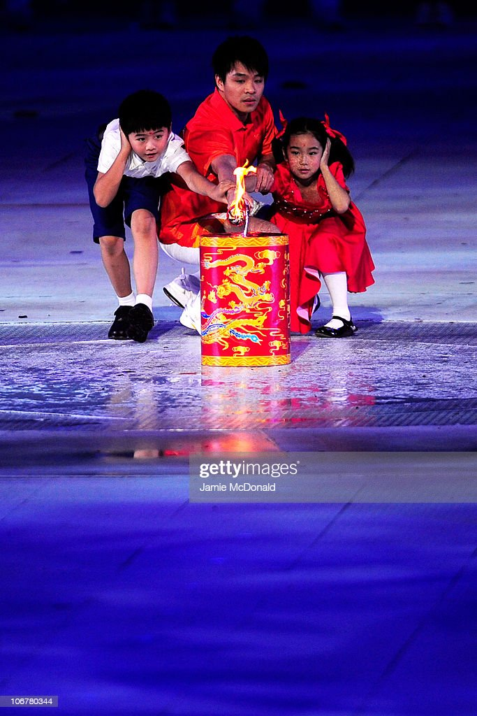 The torch bearer and children lights the games flame cauldron by a firework during the Opening Ceremony for the 16th Asian Games Guangzhou 2010 at Haixinsha Square on November 12, 2010 in Guangzhou, China.