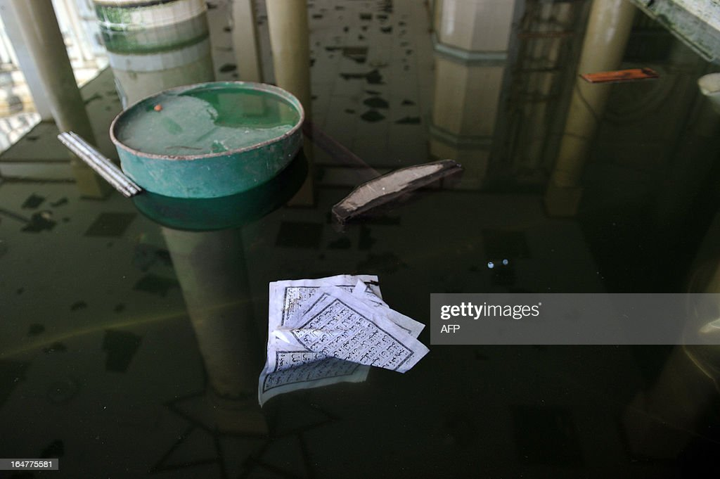 The torn pages of a Koran lie in a water tank at a partially-destroyed mosque after sectarian violence spread through central Myanmar, in Minhla, Bago division on March 28, 2013. Myanmar's Muslim leaders have appealed to President Thein Sein to take swift action to quell religious violence, accusing security forces of standing by as rioters went on a rampage. AFP PHOTO/Ye Aung THU
