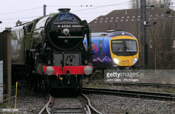 The Tornado Steam Locomotive the first to be newly built for 50 years passes by a modern passenger train after it was unveiled at the National...