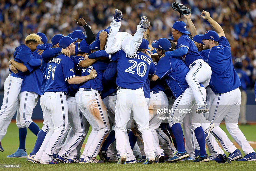 The Toronto Blue Jays celebrate the 63 win against the Texas Rangers as Ben Revere jumps on top of the pile in game five of the American League...