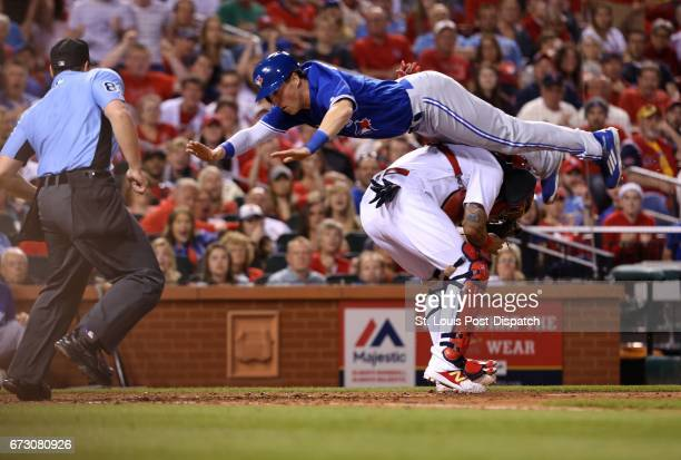 The Toronto Blue Jays' Chris Coghlan scores by leaping over St Louis Cardinals catcher Yadier Molina in the seventh inning on Tuesday April 25 at...