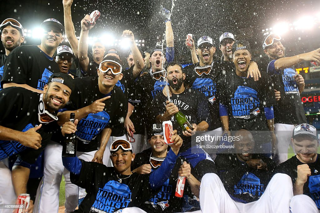 The Toronto Blue Jays pose for a team photo as they celebrate the 6-3 win against the Texas Rangers as Ben Revere #7 jumps on top of the pile in game five of the American League Division Series at Rogers Centre on October 14, 2015 in Toronto, Canada.