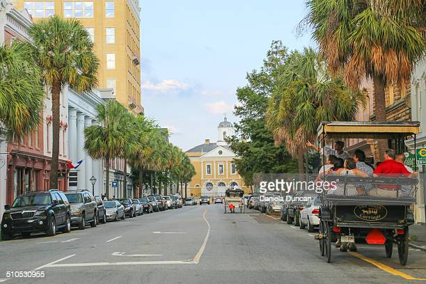 The touristy Broad Street downtown historic Charleston flanked by ubiquitous palm trees and horse carriages carrying tourists It leads to the Old...