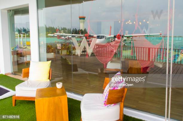 The Tower and Seaplanes of Trans Maldivian Airways are reflected at a Window of the Waiting Area Lounge at the Seadrome of Malé International Airport...