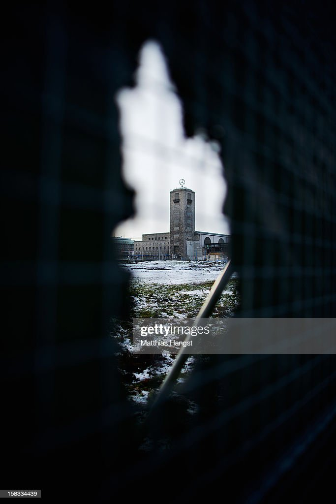 The tower of the Hauptbahnhof seen through a hole in the hoarding which surrounds the construction site of the Stuttgart 21 railway station on December 13, 2012 in Stuttgart, Germany. German state rail carrier Deutsche Bahn, which is carrying out the massive project, announced yesterday that final costs will be EUR 1.1 billion more than previously expected, bringing the total cost to EUR 5.6 billion. The project will replace the current overground, terminal station with a more efficient underground one. Critics have decried the project as too expensive and too environmentally risky.