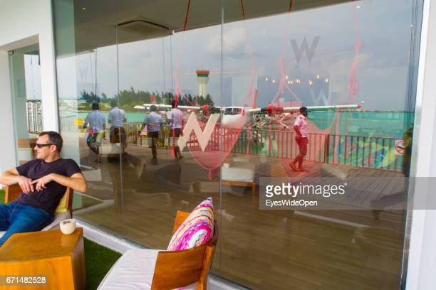The Tower Seaplanes of Trans Maldivian Airways and Local Workers are reflected at a Window of the Waiting Area Lounge with a Tourist at the Seadrome...
