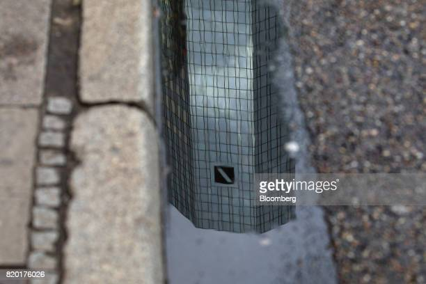 The tower skyscraper headquarter offices of Deutsche Bank AG sits reflected in a puddle in Frankfurt Germany on Thursday July 20 2017 Frankfurt has...