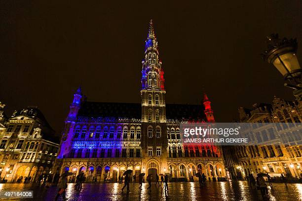 The town hall of Brussels is illuminated with the colours of the French national flag at the Brussels Grand Place on November 14 a day after deadly...