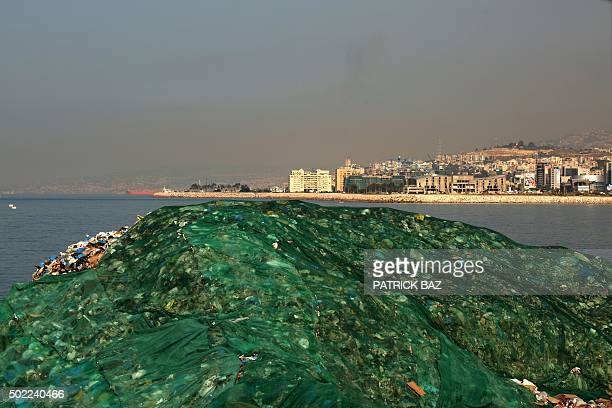 The town of Dbayeh is seen in the background behind rubbish piled up at a temporary garbage dump on a beach in Zalka north of Beirut on December 22...