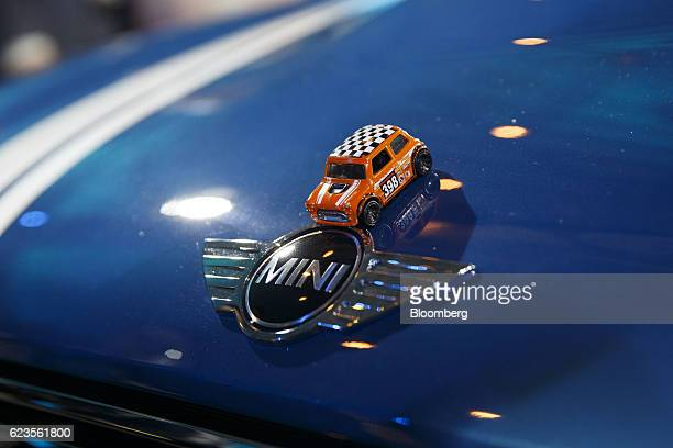The toy car in the likeness of a MINI is placed over the badge of the Bayerische Motoren Werke AG MINI Countryman compact sports utility vehicle on...