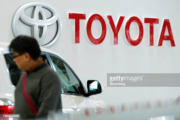 The Toyota Motor Corp logo is displayed on a wall while a visitor walks past a Highlander sportutility vehicle on display at the company's showroom...