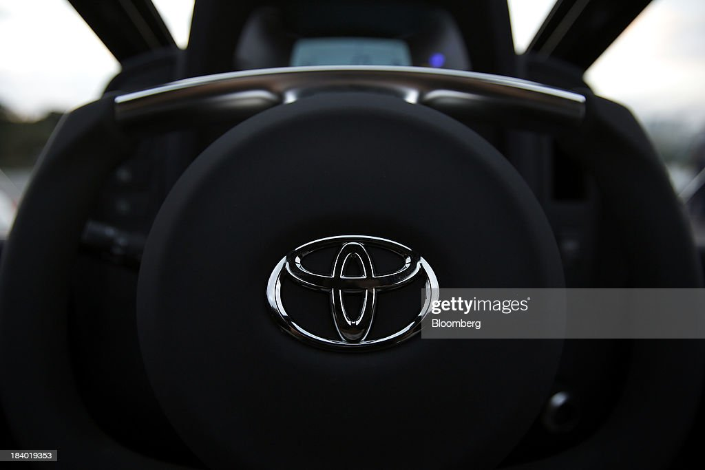 The Toyota Motor Corp. logo is displayed on the steering wheel of an i-ROAD electric personal mobility vehicle (PMV) on display during a media briefing on the company's advanced technologies in Tokyo, Japan, on Thursday, Oct. 10, 2013. Toyota, the worlds largest automaker, will introduce systems in about two years enabling cars to communicate with each other to avoid collision. Photographer: Kiyoshi Ota/Bloomberg via Getty Images