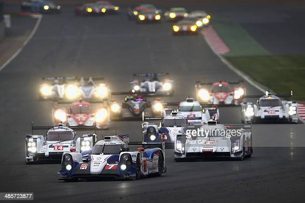 The Toyota Racing TS040 Hybrid LMP1 driven by Kazuki Nakajima of Japan Stephane Sarrazin of France and Alexander Wurz of Austria leads the pack into...