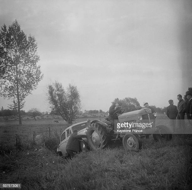 The Tractor lifts a car which fell into a ditch on the way back from vacation on August 30 1965 in NogentLeRotrou France