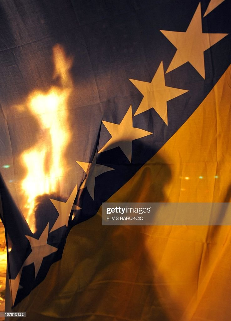 The traditional May 1st camp fire is seen through a Bosnian flag, in Sarajevo's western suburb of Ilidza, late on April 30, 2013, marking the beginning of celebrations of The International Labour Day.