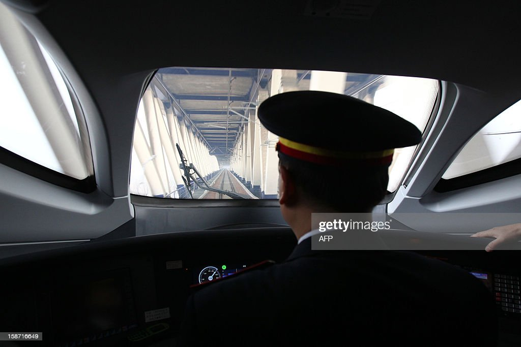The train driver of the high speed train that runs on the new 2,298-kilometre (1,425-mile) line between Beijing and Guangzhou looks through the front window in Zhengzhou train station in Zhengzhou, central China's Henan province on December 26, 2012. China started service on December 26 on the world's longest high-speed rail route, the latest milestone in the country's rapid and -- sometimes troubled -- super fast rail network. The opening of this new line means passengers will be whisked from the capital to the southern commercial hub in just eight hours, compared with the 22 hours previously required. CHINA OUT AFP PHOTO