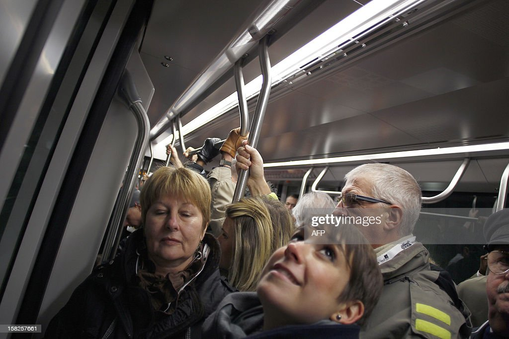 The tramway is crowed by passengers during its inaugural day, on December 12, 2012 in the northwestern city of Le Havre. 23 stations serve the 13 km network of the tramway whom carriages have been made by French engineering giant Alstom. AFP PHOTO/CHARLY TRIBALLEAU.