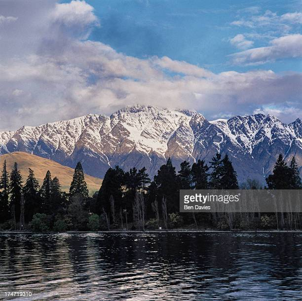 The tranquil waters of beautiful Lake Wakatipu framed by snowy mountain peaks towering trees and scenic fjords at Queenstown on New Zealand's South...