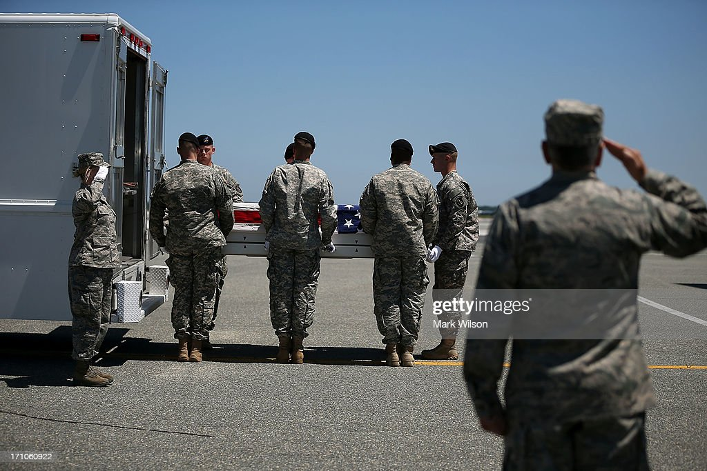 The transfer case containing the remains of U.S. Army Spc. Ember M. Alt, is moved by a U.S. Army carry team during a dignified transfer at Dover Air Force Base, on June 21, 2013 in Dover, Delaware. Spc. Alt 21, from Beech Island, S.C., was killed in Bagram , Afghanistan of wounds sustained after enemy forces attacked her unit at the air base there.