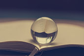 The transparent glass sphere lies on the opened notebook with a bookmark