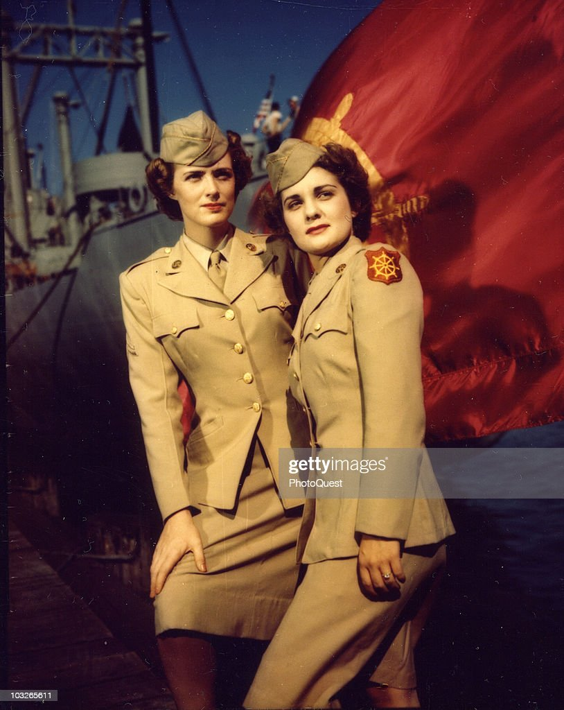 The Transportation Corps flag is an appropriate background for Corporal Beth Haddow and Pfc. Dorothy Hamilton, WACs in the Transportation Corps at the Hampton Roads Port of Embarkation, Newport News, Virginia, 1940s.