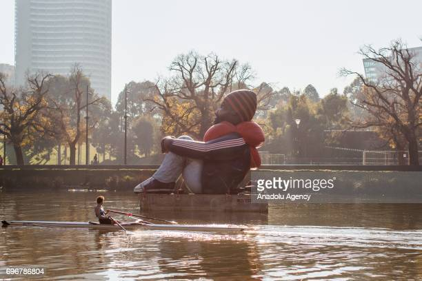 The travelling artwork titled 'Inflatable Refugee' on the Yarra River as a rower rows past on June 17 2017 in Melbourne Australia The five metrehigh...