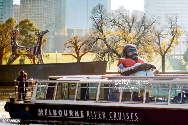 The travelling artwork titled 'Inflatable Refugee' on the Yarra River as a river cruise goes past on June 17 2017 in Melbourne Australia The five...