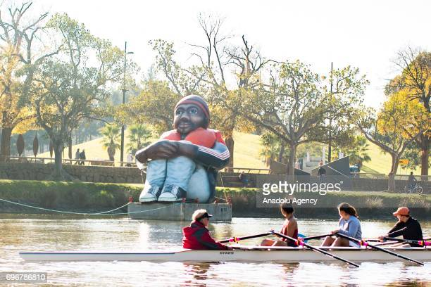 The travelling artwork titled 'Inflatable Refugee' on the Yarra River as rowers look on while rowing past on June 17 2017 in Melbourne Australia The...