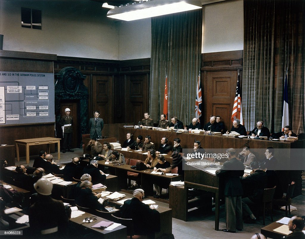 The trial takes place of SS and Sicherheitsdienst leader Ernst Kaltenbrunner (1903 - 1946, standing, left) in Room 600 at the Palace of Justice during the International Military Tribunal (IMT), Nuremberg, Germany, 19th-20th December 1945. A diagram on the left shows Kaltenbrunner's position in the hierarchy of the SS and Sicherheitsdienst. On the judges' bench are (left to right): Alexander F. Volchkov and Iona T. Nikitchenko of the USSR, Sir Norman Birkett and Sir Geoffrey Lawrence of Great Britain, Francis Biddle and John J. Parker of the USA, Henri Donnedieu de Vabres and Robert Falco of France. Kaltenbrunner was later found guilty of war crimes and crimes against humanity and sentenced to death.