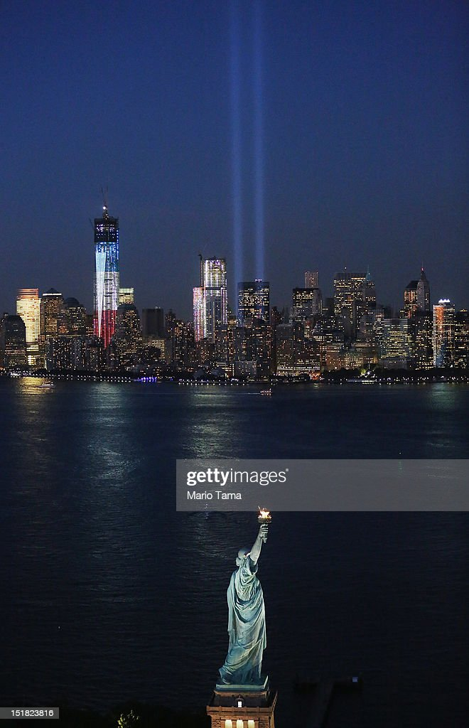 The 'Tribute in Light' and Statue of Liberty shine as One World Trade Center (L) rises under construction on the eleventh anniversary of the terrorist attacks on lower Manhattan at the World Trade Center on September 11, 2012 in New York City. New York City and the nation are commemorating the eleventh anniversary of the September 11, 2001 attacks which resulted in the deaths of nearly 3,000 people after two hijacked planes crashed into the World Trade Center, one into the Pentagon in Arlington, Virginia and one crash landed in Shanksville, Pennsylvania.