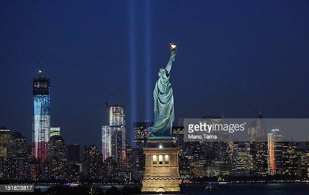 The 'Tribute in Light' and Statue of Liberty shine as One World Trade Center rises under construction on the eleventh anniversary of the terrorist...