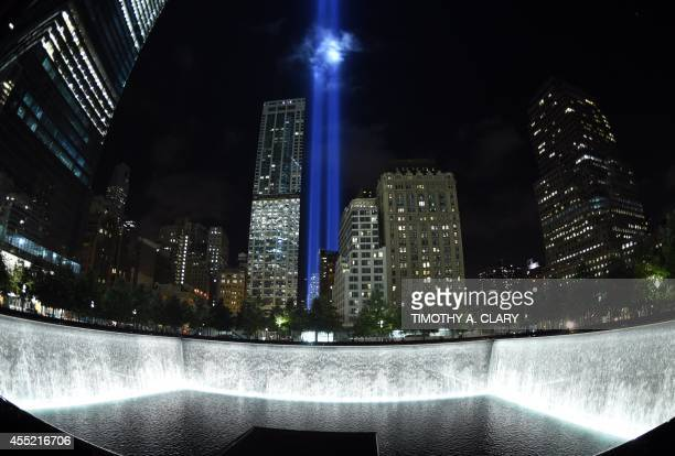 The Tribute in Light illuminates the sky behind the 9/11 Memorial waterfalls and reflecting pool in New York on September 10 the night before the...