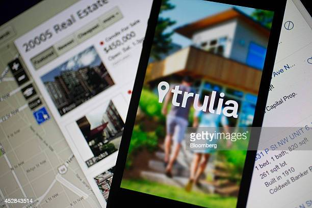 The Trulia Inc logo is displayed on an Apple Inc iPhone 5s in front of the Zillow Inc website in this arranged photograph in Washington DC US on...