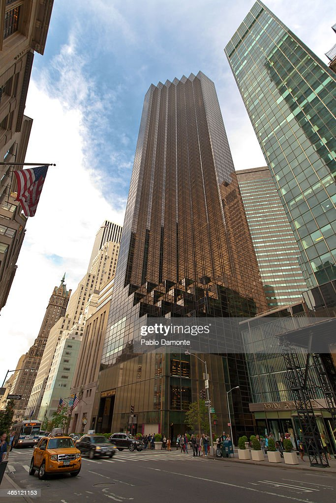 The Trump Tower is one of the icons of Fifth Avenue. Yellow typical taxi with lots of people passing by at the evening in New York City, United States of America the 5th of May of 2013