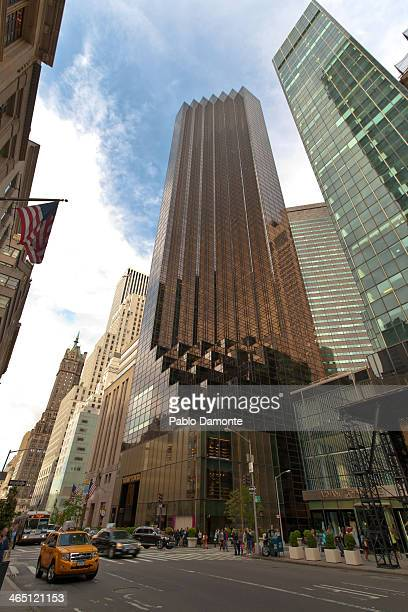 The Trump Tower is one of the icons of Fifth Avenue Yellow typical taxi with lots of people passing by at the evening in New York City United States...
