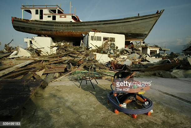 The tsunami left this huge fishing boat perched on the ruins of a house in Lam Pulo Banda Aceh Indonesia A young girl plays in the ruins while her...