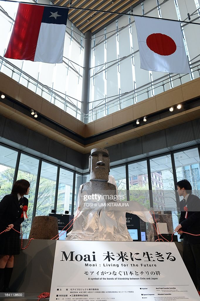 The tsunami-devastated town of Minamisanriku's Sizugawa high school students Chie Shuto (L) and Kazuna Goto (R) unveil the new 'Moai' statue (C), modelled on the mysterious carvings at Easter Island, during its preview in Tokyo on March 20, 2013. The giant present crossed the ocean from Chile as the town's original was destroyed in March 11 quake-sparked tsunami disaster in 2011. AFP PHOTO / TOSHIFUMI KITAMURA