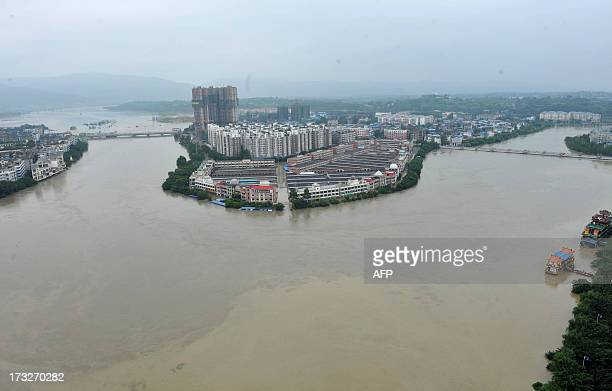 The Tuo river floods Jintang county southwest China's Sichuan province on July 11 2013 Heavy rain across China has left at least 28 people dead and...