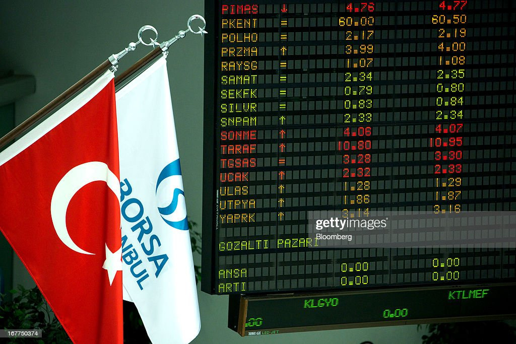 The Turkish national flag, left, and the Borsa Istanbul flag hang alongside financial data displayed on electronic boards inside the Borsa Istanbul, the stock exchange in Istanbul, Turkey, on Monday, April 29, 2013. Turkey is building a financial district in Istanbul and merged the 28-year-old Istanbul Stock Exchange with gold and derivatives exchanges into Borsa Istanbul this month. Photographer: Kerem Uzel/Bloomberg via Getty Images