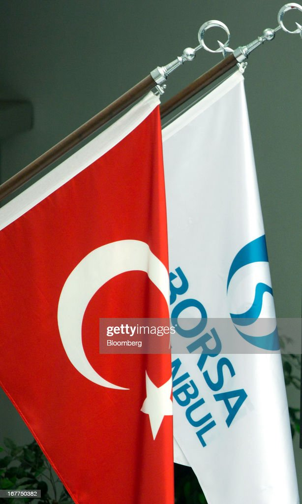 The Turkish national flag, left, and the Borsa Istanbul flag hang inside the Borsa Istanbul, the stock exchange in Istanbul, Turkey, on Monday, April 29, 2013. Turkey is building a financial district in Istanbul and merged the 28-year-old Istanbul Stock Exchange with gold and derivatives exchanges into Borsa Istanbul this month. Photographer: Kerem Uzel/Bloomberg via Getty Images